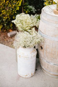 Rustic Milk Jugs filled with Baby's Breath - On http://www.StyleMePretty.com/2014/03/27/whimsical-woodland-garden-wedding/ Mason And Megan Photography - masonandmegan.com