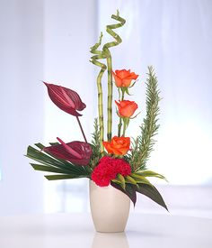 pretty floral arrangements | Flower arrangement in vivid bright colours in a container. Modern and ...