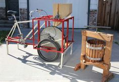 A pedal-powered apple crusher that pulls around like a bike trailer, then locks in place to crush up the apples for pressing. The chain drives a heavy flywheel (an old bicyle wheel filled with concrete), which keeps steady power going to the crusher, an oak cylinder with stainless steel screwheads sticking out to shred the fruit.