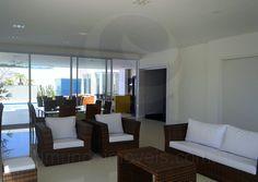 A sala para dois ambientes integra o estar, decorado com mobiliário em fibra sintética, e a sala de jantar. O primeiro ambiente, mais próximo à escada, é bem iluminado graças ao pé direito duplo e da imensa janela que permite que a luz natural permeie por toda a sala.