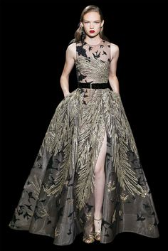 Long split and sleeveless dress in guipure, brids and feathers embroidered with black and anthic gold silk threads, sequins and crystals.