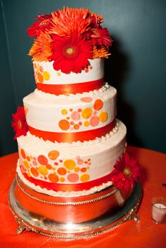 Colorful red and orange themed wedding cake.   Photo by Coleman Shots www.engagingeventsobx.com #engagingeventsobx #weddingcake