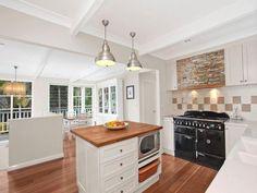 stacked stone rangehood polished timber floors white shaker cupboards pendant lights black cooker range checker tiles