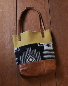 The perfect blend of rustic and modern. Salvaged Pendleton blanket wool is pieced together in clean lines with rich leather. Fully lined in cotton canvas with two interior pockets and finished with leather straps and brass hardware. This tote can easily accommodate books, magazines, newspapers, a change of clothes or simply function as your everyday go-to purse. approximate dimensions: 12 wide by 14 high with 3 boxed corners at the base. 11 strap drop. You will receive the exact bag…