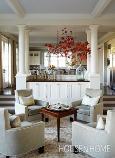 To separate the space between the kitchen and dining areas without closing them off entirely, designer Sarah Richardson installed built-in cabinets topped with Tuscan columns. | Photographer: Angus Fergusson