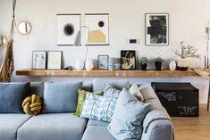 Een grijze hoekbank en een houten wandplank met posters bij Elyna en Patrick uit aflevering 2, seizoen 8 | Make-over door: Fietje Bruijn | Fotografie Barbara Kieboom