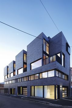 Designed for commercial or residential use, the townhouses present a transparent facade at street level.