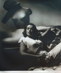 "Gene Tierney with sculpture (1944). Photograph by George Hurrell.  Hurrell made his mark early by re-inventing the celebrity still. Trained as a painter, he began his switch to photography by taking what he called ""social portraits"" of the high society of Laguna Beach. Ever adaptive to the look and technology of the age, Hurrell produced highly glamorized, black-and-white portraits of stars like Greta Garbo, Joan Crawford, and here Tierney."