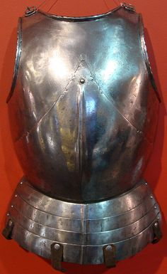 """Cavalry breast-plate """"alla tedesca"""", Italian, possibly Brescia, c 1470, the upper plate globose and with outward turns at the neck and arms, the turned flanges hammered in an indented pattern, the lower plate moving on a single central sliding rivet and on a pair of internal leathers at the sides, the lower plate formed with a fluted low medial ridge, the upper edges cut with cusped ornament and small linear design, later skirt of four lames. H: 50 cm, W.: 34.5 cm,  Wt.: 2810 g."""
