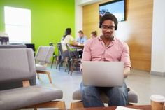 Person wearing headphones sits alone in open office, smiling while working on laptop