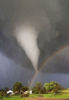 Storms Tornadoes: A white tornado descends from a dark storm cloud toward a rainbow, while the Sun peeks through a clear patch of sky. Photo by storm-chaser Eric Nguyen, June 2004.