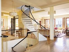 Bette Midler's NYC Penthouse Apartment  STAIRWAY Stairways with brass balusters connect the three levels of the penthouse; Fernando Santangelo designed the pendants and the column-mounted lights.