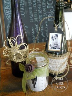 Burlap, twine, lace, ribbon, and glitter make an eclectic decorative mix for wedding centerpieces using Mason jars and wine bottles.