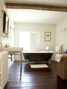 A cozy farmhouse bathroom with a dark wooden floor, a black clawfoot bathtub, a white sink and a mirror. Traditional Bathroom, Georgian Homes, Georgian Interiors, Bathroom Farmhouse Style, Bathroom Styling, Farmhouse Bathroom Vanity, Bathroom Design, Beautiful Bathrooms, Farmhouse Bathroom Decor