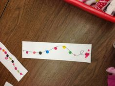 """Use dot markers or fingerprints to make a string of lights. Put a dot on the left and right edge of the paper.  The kids connect the dots with a squiggly line and add the """"lights"""".  The pieces can be put together to make a long string of lights around a door.  SO Cute!"""