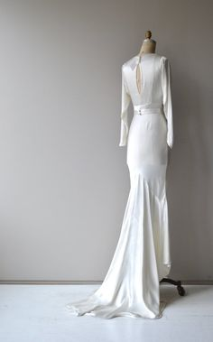 Vintage 1930s liquid silk wedding gown with graceful draped neckline, long slender sleeves, inverted seam bodice, belt, long elegant skirt and extending train. --- M E A S U R E M E N T S ---  fits like: xs shoulder: 14 bust: 32 waist: 27 hip: up to 40 length: 59 at the front with long extending train brand/maker: n/a condition: a dark mark on the extended train (can be altered, dress shortened), sold as is. ✩ layaway is available for this item  To ensure a good fit, please read the...