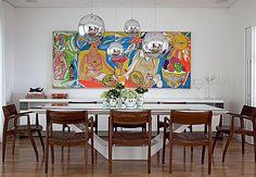 Os quatro pendentes metálicos de Tom Dixon foram instalados sobre a mesa de jantar, deixando o ambiente ainda mais moderno