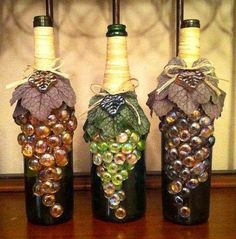 "Wine bottles decorated with glass marble ""grapes"" glued to the bottles. Necks wrapped in raffia. Artificial grape leaves add texture and dimension."