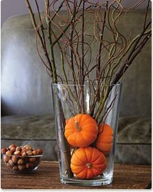 Mini orange pumpkins anchor long twigs in a glass vase