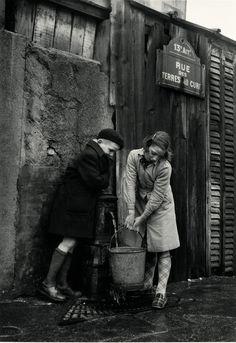 Niños cogiendo agua de una fuente rue des Terres-au-Curé, París. 1954.  SABINE WEISS