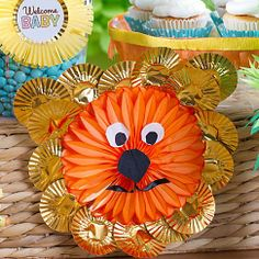 Paper fan + baking cups = king of the jungle to welcome the new cub! Click for lots more baby shower candy buffet ideas that work for a girl or a boy shower.