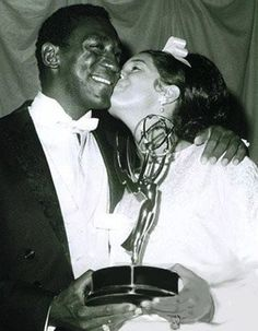 "Bill Cosby being congratulated by his wife Camille on his first Emmy win for ""I Spy"" in 1966. Cosby was the first Black actor to star in a leading role in an American television drama. He won the first of what would be three consecutive Emmys for ""Outstanding Lead Actor in a Drama Series."""