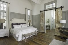 Master bedroom: Barn doors, upholstered headboard, vaulted butt-joint ceiling with painted trusses, hardwood floors
