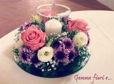 Centrotavola con rose, lisianthus e margherite; candela centrale in vaso di vetro.