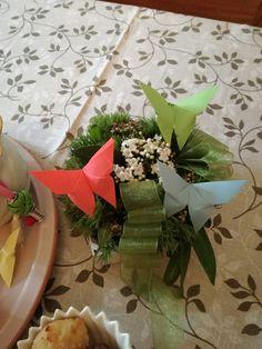 Farfalle origami si posano su fiori in scatola.