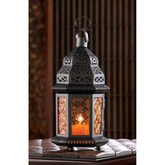 The colored pattern glass of this exotic tabletop candle lantern will shine when a candle of your choice is lit inside. Featuring intricate cutout metalwork and a hinged door for easy lighting, this l