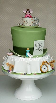 A 3 tier cake designed to coordinate with the wedding theme of the Mad Hatter's Tea Party! Hand modelled sugar decorations include a fob watch, drink me vial, eat me biscuits, signs and a teacup and saucer with a cute dormouse perched inside.
