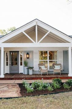 Charming beach house exterior with covered front porch and wicker chairs.
