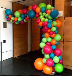 organic texture half balloon arch in robins egg blue, orange, lime green and wildberry