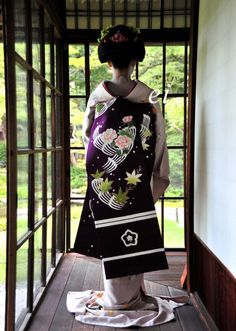 You can tell she's a maiko by the color of her inner kimono. Maiko will commonly wear red or white patterned collars, whereas geisha will wear plain white collars