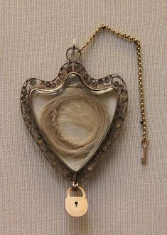 a gold locket holding a piece of queen marie antoinette's hair from the british museum. often pieces like this were mourning jewelry, and i think the tradition should come back.