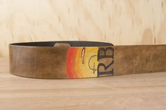 Super cool custom guitar strap with a sunrise (or sunset?) and initials on it.   I love how the warm brown looks with the red, orange and yellow of the sunrise.