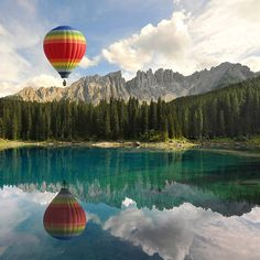 Amazing and vivid landscape photograph of a hot air balloon reflected in beautiful blue waters below it. Image by Franco Mottironi.