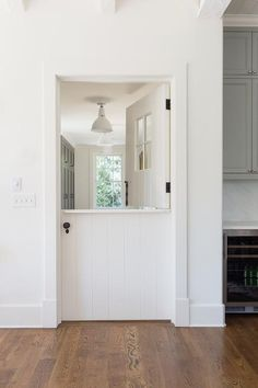 A white shiplap dutch door opens to a white and gray mudroom fitted with gray lockers lit by a white industrial pendant.