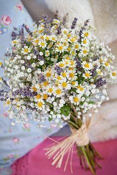 Pâquerettes, fleurs des champs et lavandes : on est en plein dans le thème estival recherché. Pour un bouquet qui sent bon la Provence, le tout attaché avec de la paille pour un esprit champêtre.