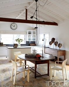 Clean and contemporary: This kitchen is open and airy with center island and glass cabinets above and white painted cabinetry below