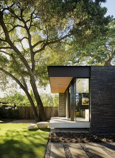 Outdoor, Trees, Side Yard, Back Yard, Boulders, Grass, Walkways, and Wood Fences, Wall The master bedroom was raised and cantilevered so as not to disturb the mature oak tree roots. Boulders are used as steps to the lawn.