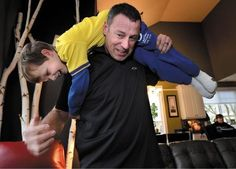 Cole Vukich gets a firemen's carry from his father, West Pierce firefighter Steve Vukich, at their University Place home on Wednesday. Cole's leukemia is in remission.