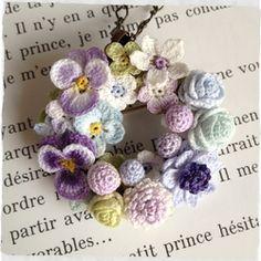 レース編みのちいさなお花、パンジーやバラ、アネモネなどたくさん集めてリース型に仕上げました。ネックレスまたはブローチとしてお使いいただけます。直径約4.8cm