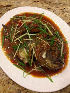 Fried fish with spicy sauce, ginger, garlic, and green onion