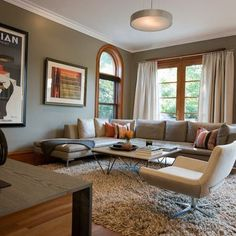 Fab light fixture and rug mute the honey oak trim in this living room.