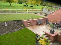 A garden transformation with brick retaining walls, steps,sandstone patio and vegetable beds by SilverBirch Gardens Ltd