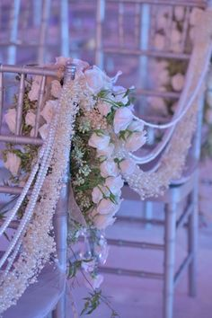 Strands of pearls and flowers decorate the seats along the aisle