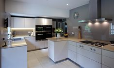 Miele ovens are complemented by the Gaggenau induction and gas cooktops. A back painted glass splashback in Farrow & Ball 'Charleston Grey' perfectly matches the walls.