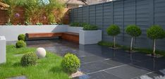 ultra low maintenace garden with slate paving and hardwood screen and raised beds modern grey painted fences