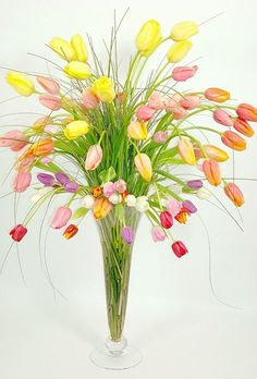 Eye-catching arrangement that would be great for decorating a spring wedding ceremony.  This design uses tulips in multiple colors along with lily grass. Tulips stems often bend (towards light), so this design takes advantage of this!